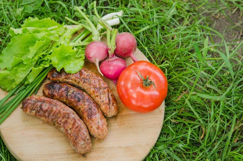 Piec na grillu warzywa na starym drewnianym tle i kiełbasa Odg?rny widok zdjęcie stock