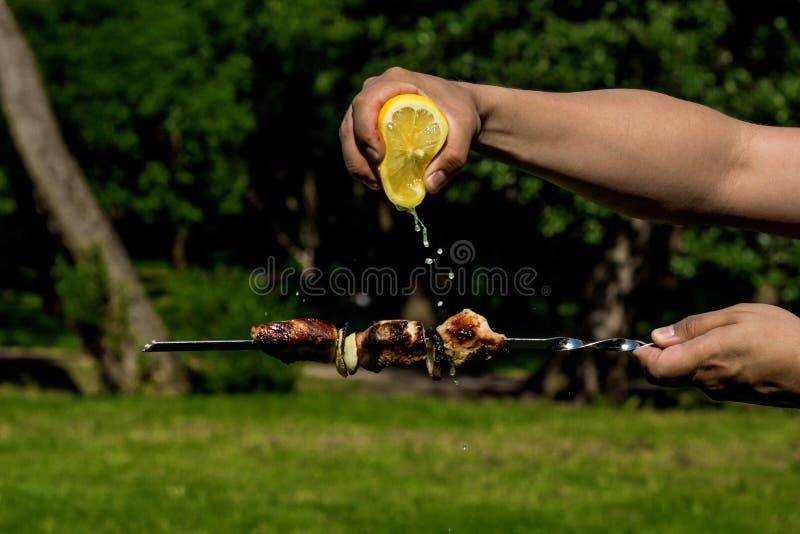 Piec na grillu wieprzowin skewers z cytryną Facet gniesie cytryna sok na kebabie obrazy royalty free