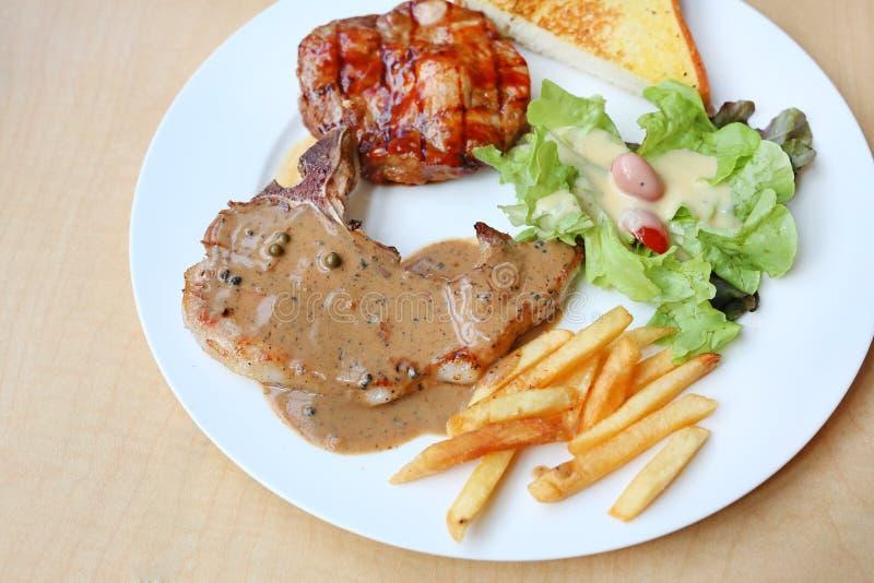 Piec na grillu wieprzowin warzywa na talerzu przeciw drewnianemu tłu i mięso zdjęcia stock