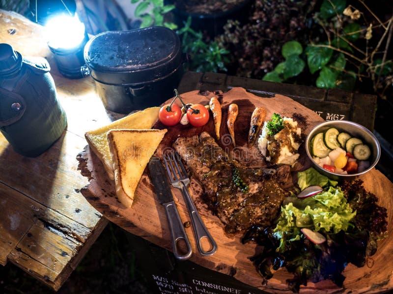 Piec na grillu wieprzowina stek z zalewami, warzywami sałatki i brei grulą w obozie, zdjęcia stock