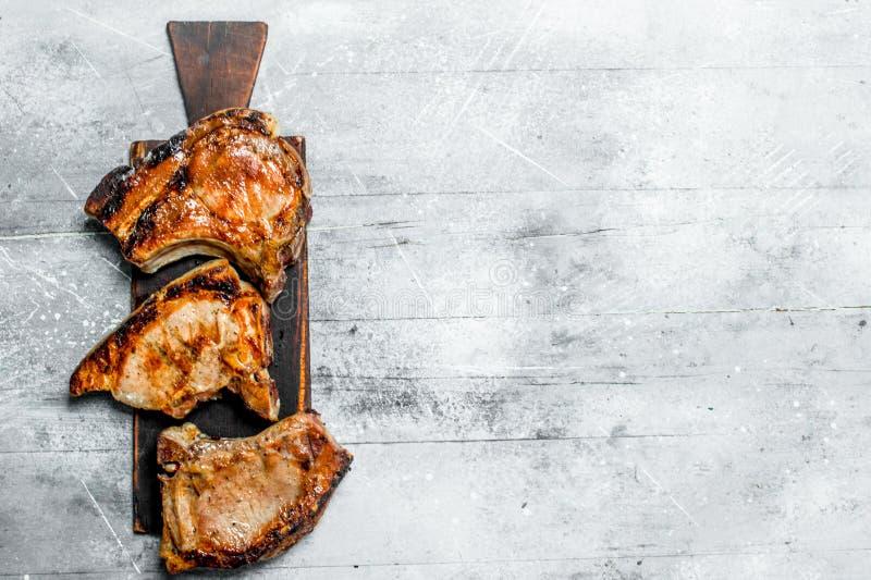 Piec na grillu wieprzowina stki na tnącej desce fotografia stock
