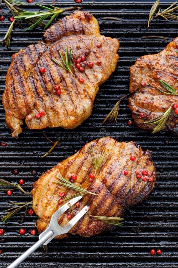 Piec na grillu wieprzowina stki, wieprzowiny szyja z dodatkiem ziele i pikantność na grilla talerzu, odgórny widok, w górę obraz royalty free