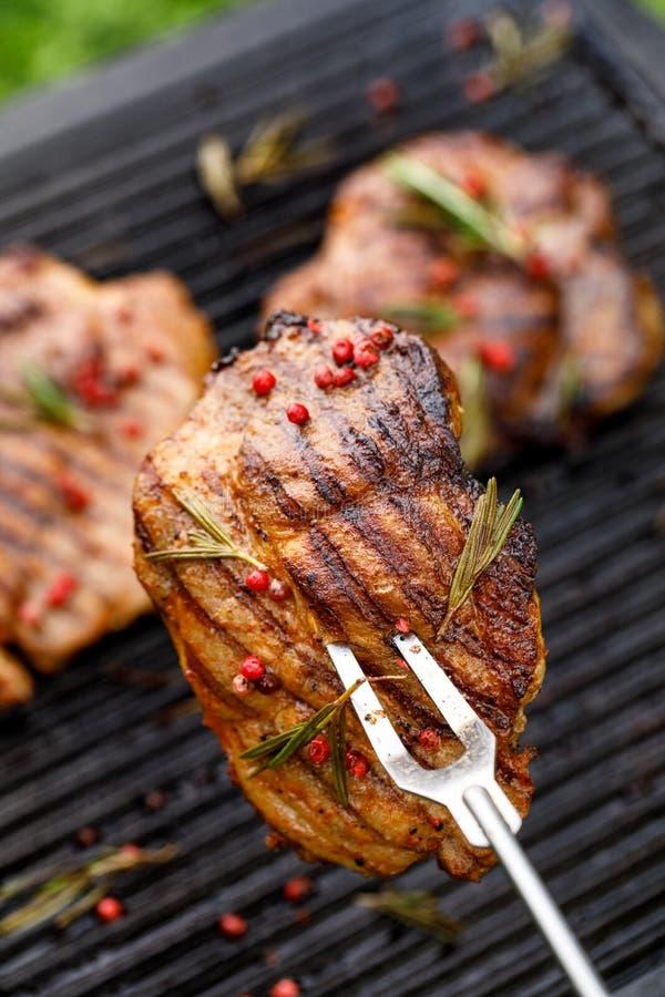 Piec na grillu wieprzowina stki, wieprzowiny szyja z dodatkiem ziele i pikantność na grilla talerzu, odgórny widok, w górę obraz stock