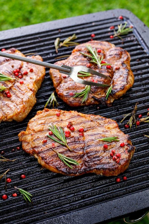 Piec na grillu wieprzowina stki, wieprzowiny szyja z dodatkiem ziele i pikantność na grilla talerzu, odgórny widok, w górę zdjęcie royalty free
