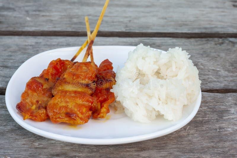 Piec na grillu wieprzowina z kleistymi ryż w bielu talerzu jest jedzeniem który jeść wolą Tajlandzcy ludzie fotografia royalty free