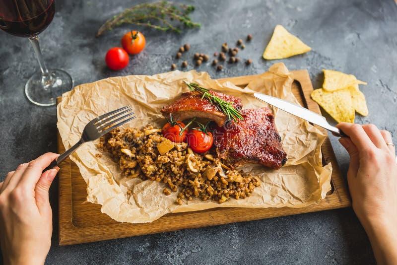 Piec na grillu wieprzowina ziobro, gryka z pieczarką i pomidory na drewnianych rękach z cutlery, rocznik tnącej deski kobiety i Z fotografia royalty free