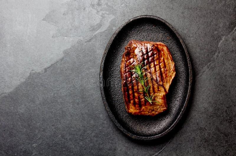 Piec na grillu wołowina stek na czerni obsady żelaza talerzu Tło z kopii przestrzenią Grill, bbq wołowiny mięsny tenderloin Odgór zdjęcia royalty free