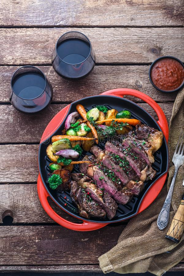 Piec na grillu wołowina stek na grilla żelaza niecce na drewnianym tle zdjęcia royalty free