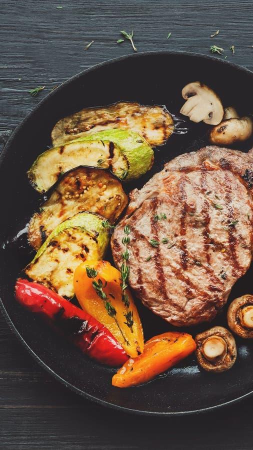 Piec na grillu wołowina stek i piec warzywa na ciemnym drewnianym stole obraz stock