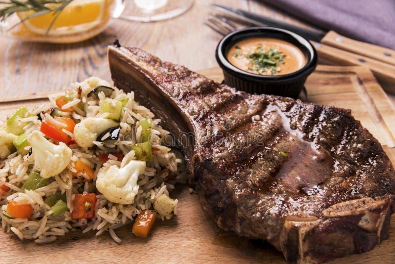 Piec na grillu wołowina stek na kości striploin z ryż i warzywami fotografia stock