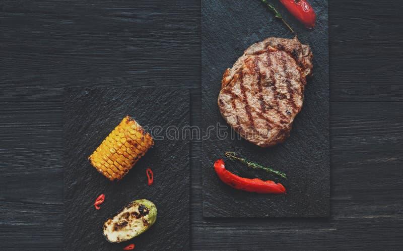 Piec na grillu wołowina stek na ciemnym drewnianym stołowym tle, odgórny widok zdjęcia royalty free