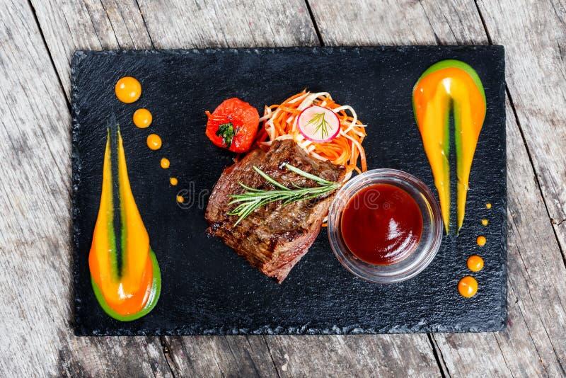 Piec na grillu wołowina stek z świeżą sałatką up i bbq kumberlandem na kamienia łupku tle na drewnianym tła zakończeniu rozdaje g obraz stock