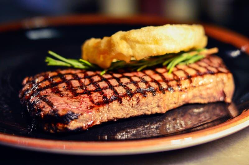Piec na grillu wołowina stek z rozmarynami i Smażącymi Cebulkowymi pierścionkami obrazy stock