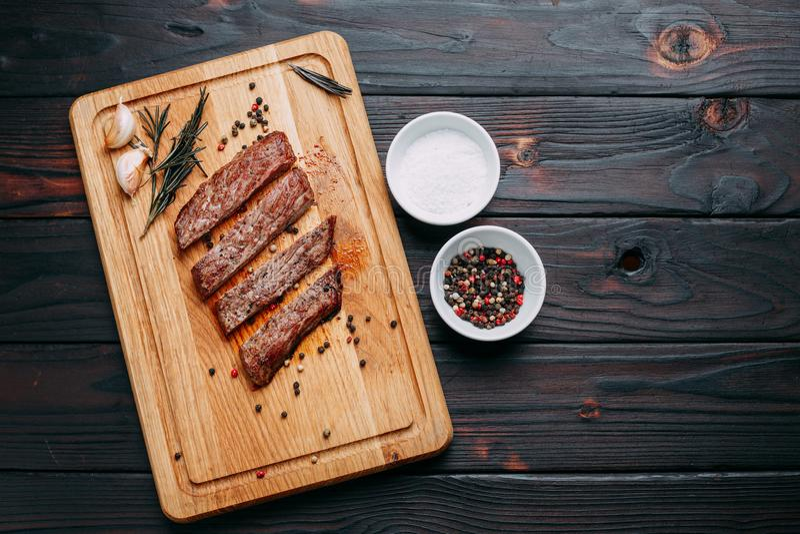 Piec na grillu wołowina stek z ziele i pikantność na tnącej desce Odgórny v obrazy royalty free