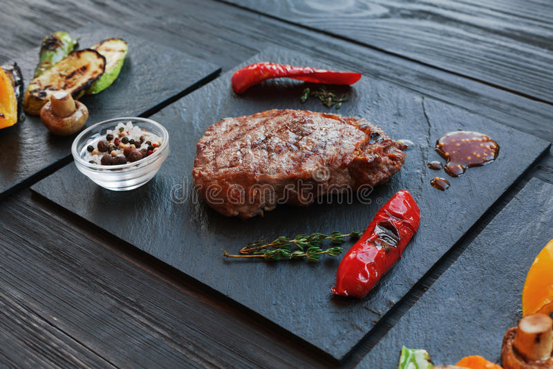 Piec na grillu wołowina stku zbliżenie na ciemnym drewnianym stołowym tle obrazy stock