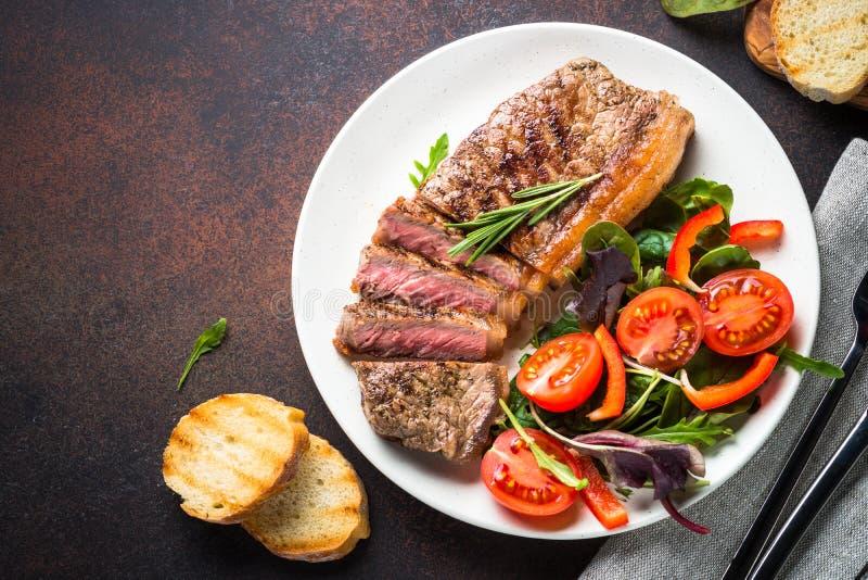 Piec na grillu wołowiny striploin stek z świeżym sałatkowym odgórnym widokiem fotografia stock