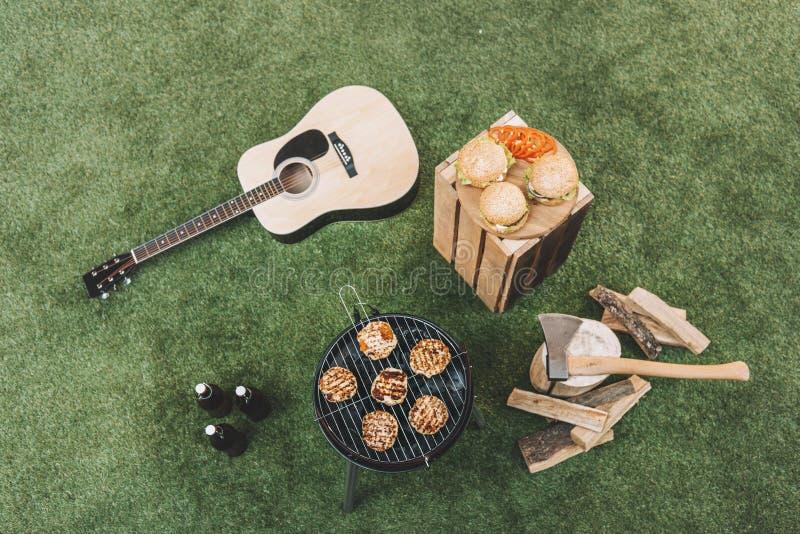 Piec na grillu z mięsem, hamburgerami na drewnianej desce, piwnymi butelkami i gitarą na trawie, zdjęcia stock
