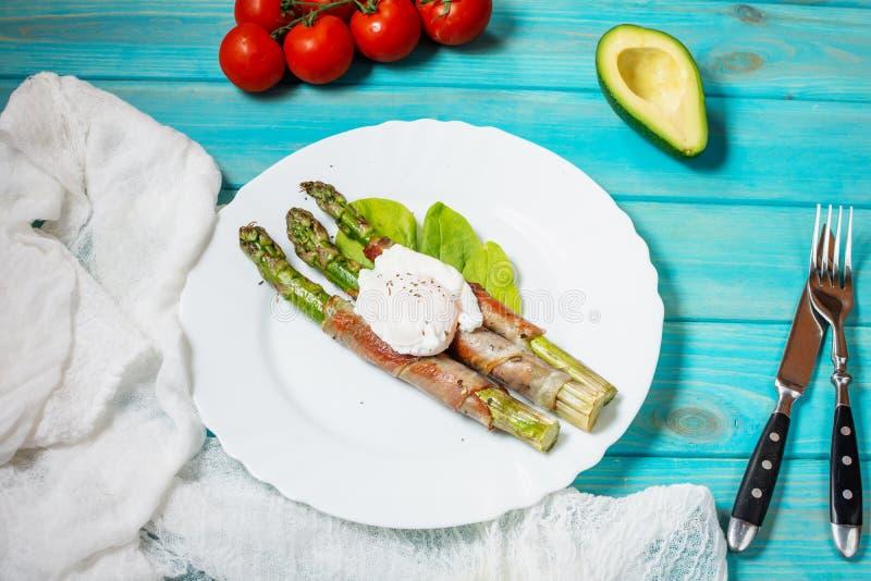 Piec na grillu zielony asparagus zawijający z bekonem, Benedict kłusował jajko na błękitnym drewnianym tle fotografia royalty free