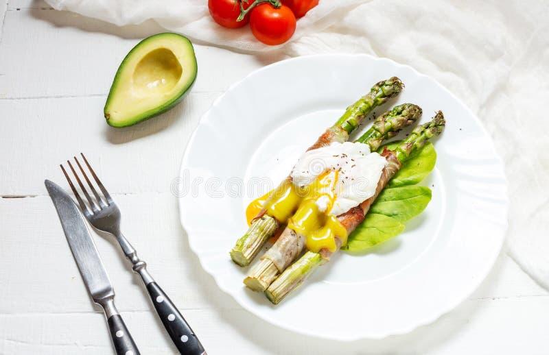 Piec na grillu zielony asparagus zawijający z bekonem, Benedict kłusował jajko na białym drewnianym tle fotografia stock