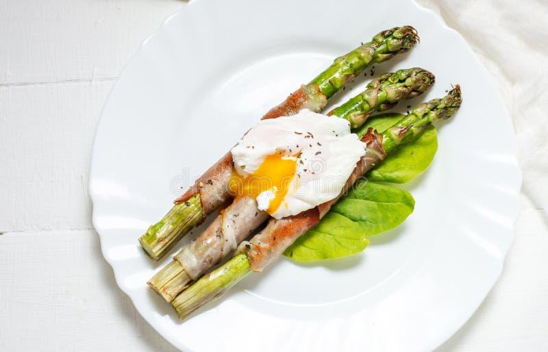 Piec na grillu zielony asparagus zawijający z bekonem, Benedict kłusował jajko na białym drewnianym tle obrazy stock