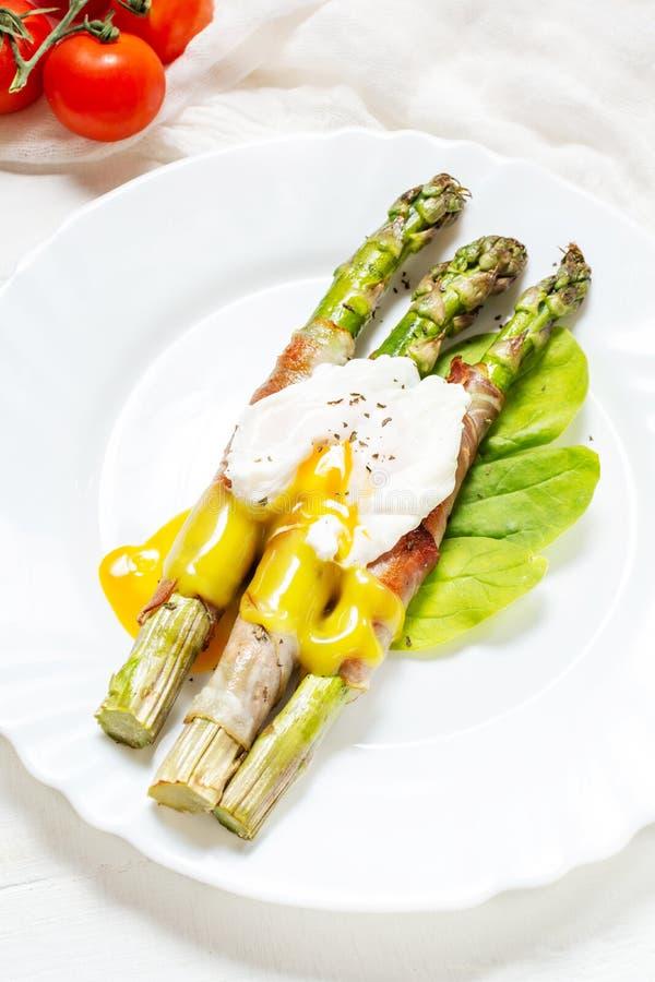 Piec na grillu zielony asparagus zawijający z bekonem, Benedict kłusował jajko na białym drewnianym tle obraz stock