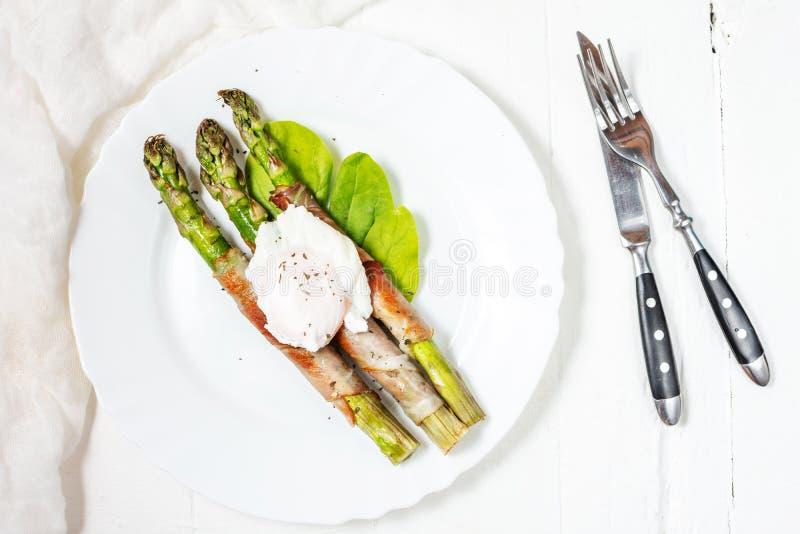 Piec na grillu zielony asparagus zawijający z bekonem, Benedict kłusował jajko na białym drewnianym tle ?niadanie obraz stock