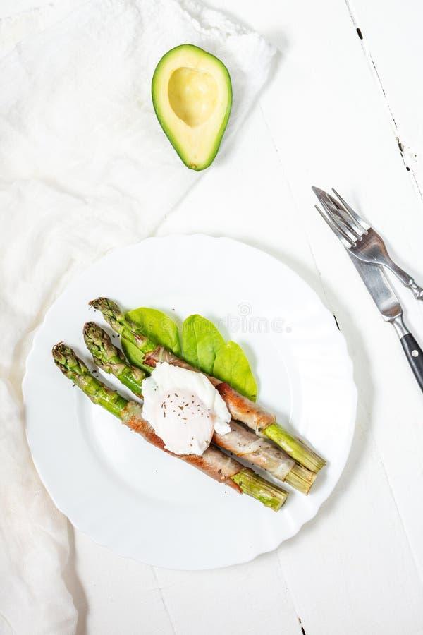 Piec na grillu zielony asparagus zawijający z bekonem, Benedict kłusował jajko na białym drewnianym tle ?niadanie zdjęcia stock