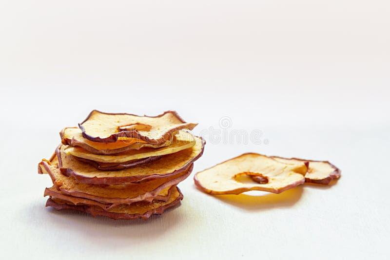 Piec odwodneni jabłko plasterki brogujący na białym drewnianym stole Domowej roboty sucha owoc szczerbi się, jesień spadku przeką zdjęcie royalty free