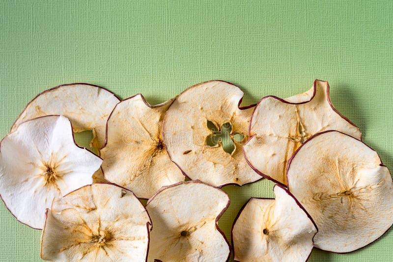 Piec Odwodneni wysuszeni jabłka Szczerbią się nad zielonym tłem z kopii przestrzenią zdjęcie royalty free