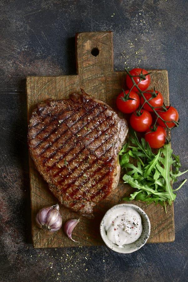 Piec organicznie rancho wołowiny stek z warzywami i czosnku kumberlandem na drewnianej tnącej desce Odgórny widok z kopii przestr obrazy stock