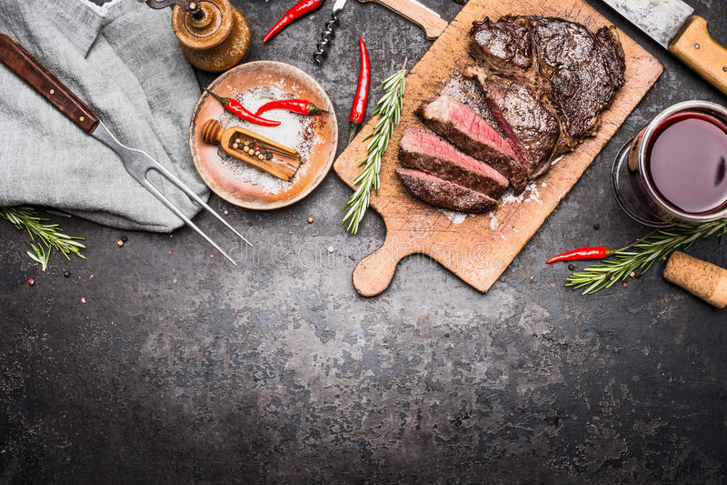Piec pokrajać grilla stek na drewnianej tnącej desce z winem, podprawą i mięsnym rozwidleniem na ciemnym rocznika metalu tle, odg obraz stock