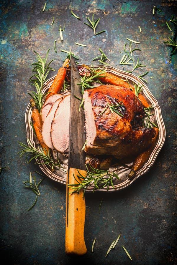 Piec pokrajać wieprzowina baleron z kuchennym nożem i pieczonymi warzywami na ciemnym nieociosanym tle obrazy stock