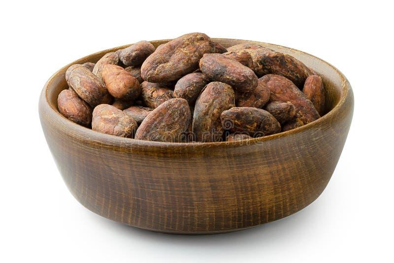 Piec unpeeled kakaowe fasole w brązu drewnianym pucharze na bielu zdjęcie royalty free