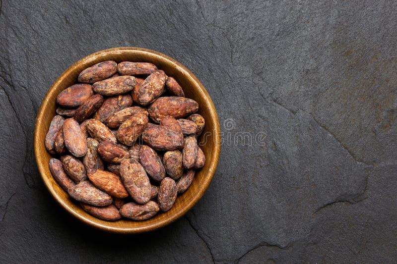 Piec unpeeled kakaowe fasole w brązu drewnianym pucharze na czerń łupku z góry Przestrze? dla teksta fotografia stock