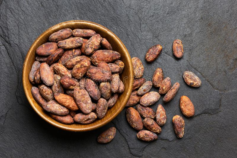 Piec unpeeled kakaowe fasole w brązu drewnianym pucharze obok unpeeled kakaowego beansl odizolowywającego na czerń łupku z góry zdjęcia stock