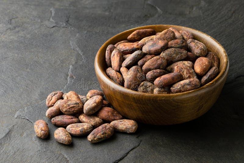 Piec unpeeled kakaowe fasole w brązu drewnianym pucharze obok stosu unpeeled kakaowe fasole na czerni krytykują obrazy royalty free