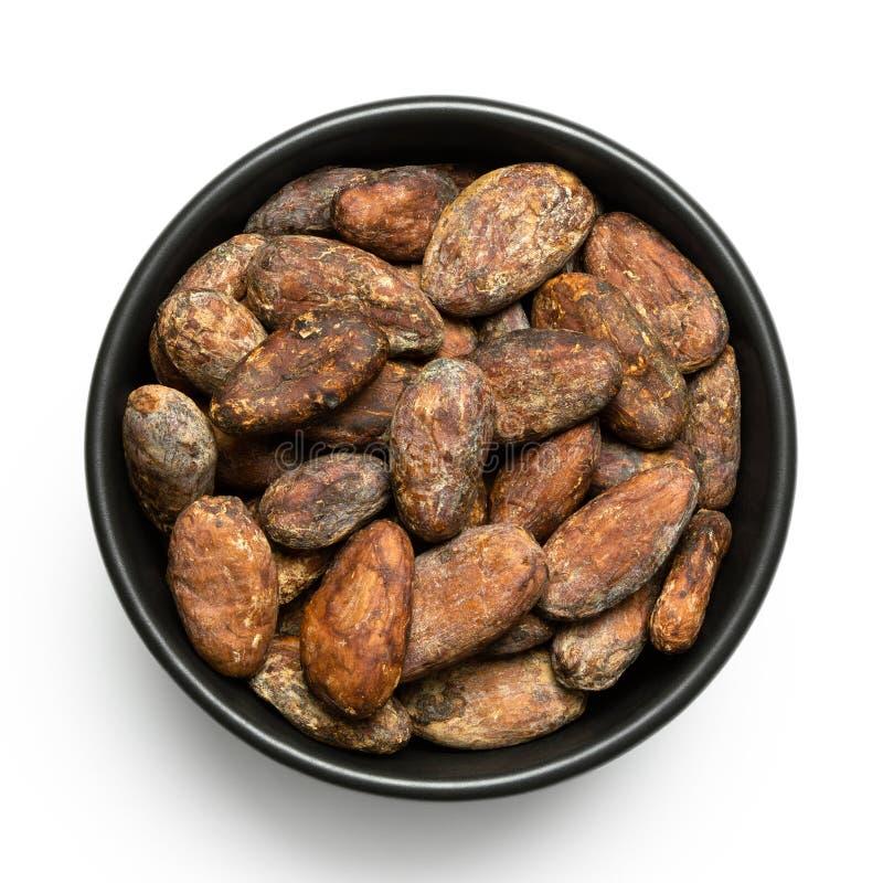 Piec unpeeled kakaowe fasole w czarnym ceramicznym pucharze na bielu z góry zdjęcie royalty free