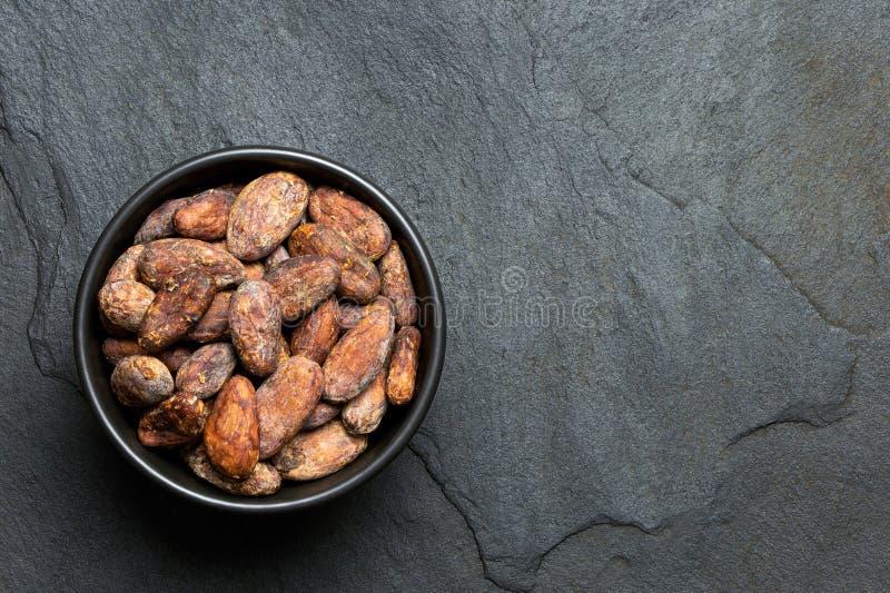 Piec unpeeled kakaowe fasole w czarnym ceramicznym pucharze na czerń łupku z góry Przestrze? dla teksta obraz stock