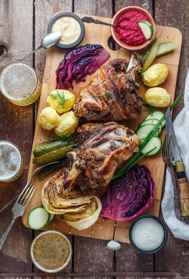 Piec wieprzowina knykcia eisbein z braised kapustą, grulą, zalewami, upadem i piwem gotowanymi, odgórny widok zdjęcia royalty free