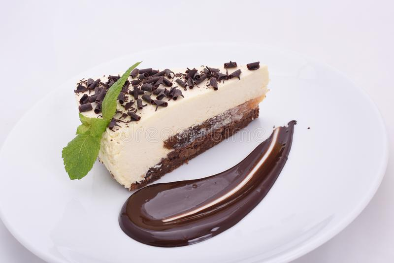 Piece of appetizing cheesecake with chocolate chips on a white plate stock photo