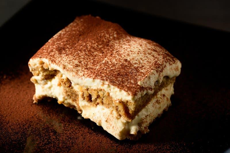 Piece of appetizing tiramisu cake on plate in close up stock images