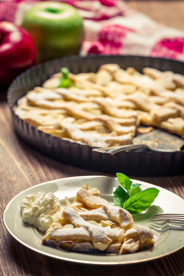 Piece of apple pie with cream on a plate royalty free stock photo