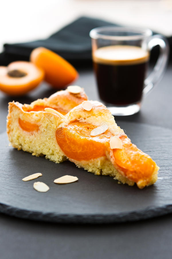 A piece of apricot cake with almond slivers on a black round slate. Two halves of an apricot and a black napkin in the background, a cup of espresso in the stock photo