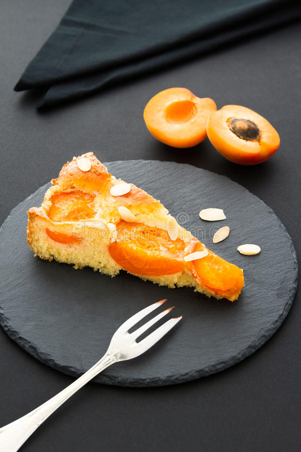 A piece of apricot tart with almond slivers on a black slate. Two halves of an apricot and a black napkin in the background, a fork in front of the cake stock image