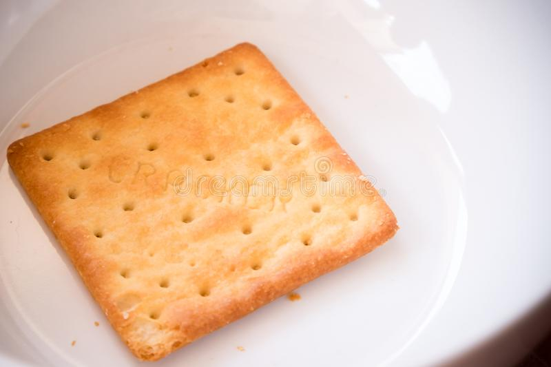 Piece of baked salty whole wheat crispy thin cracker in the white bowl. delicious snack for after breakfast, tea break afternoon. stock photos