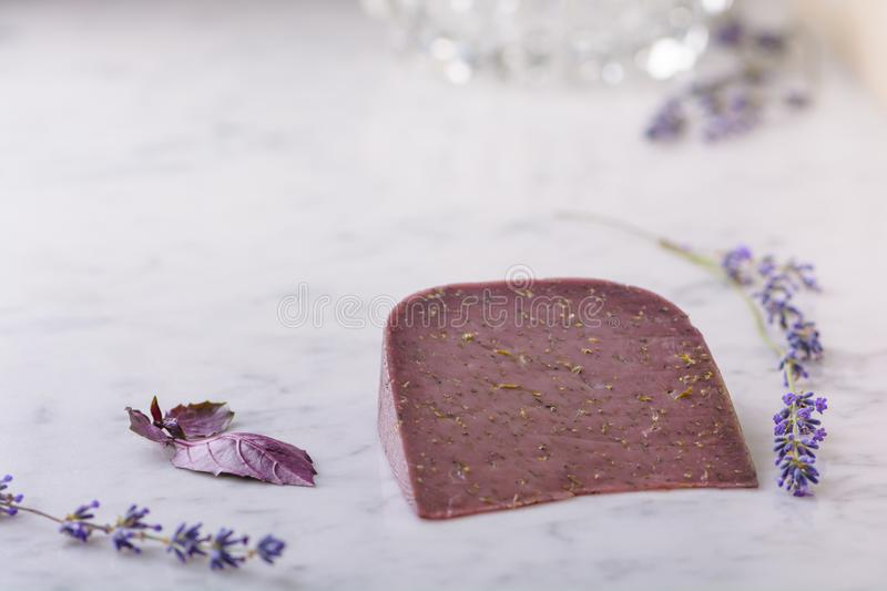 Piece of Basiron lavender cheese, lavender flowers and basil leaves on white marble table top stock images