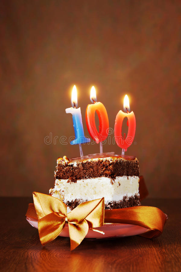 Piece of Birthday Cake with Burning Candle as Number One Hundred. Piece of Birthday Chocolate Cake with Burning Candle as a Number One Hundred on Brown royalty free stock photography