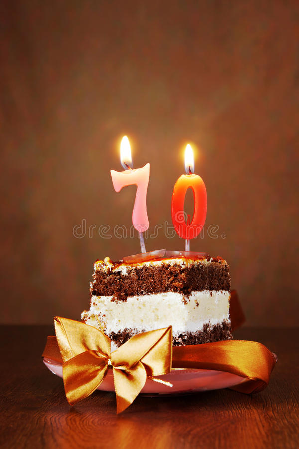 Piece of Birthday Cake with Burning Candle as Number Seventy stock photos