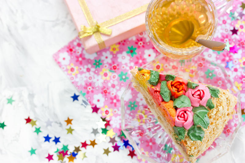 Piece of birthday cake, tea in cup, gift box and colorful confetti royalty free stock image