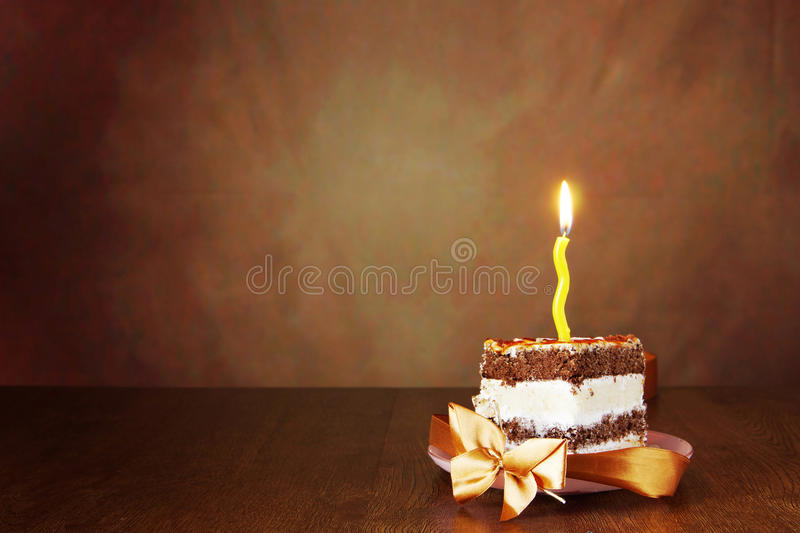 Piece of birthday chocolate cake with one burning candle. Against brown background stock photos